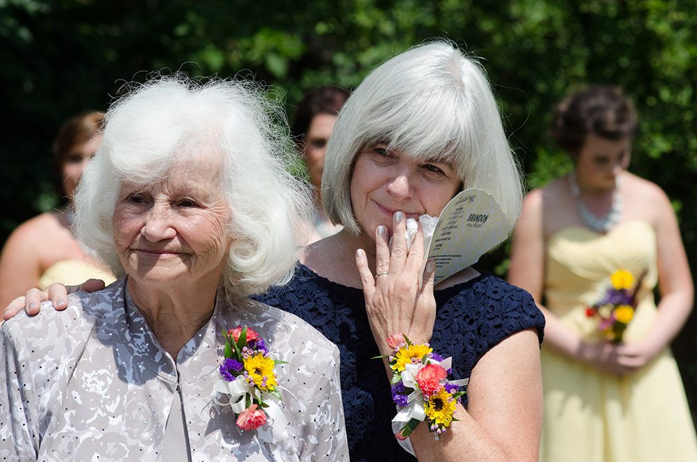 Photo of the mother and grandmother of the bride watching her come down the aisle.  Love the expressions on their faces
